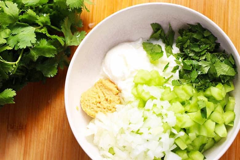 A bowl with yogurt, cucumber, garlic, cilantro and onion