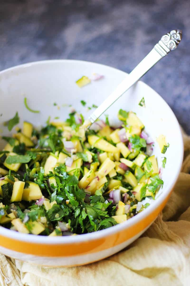 A bowl of chopped zucchini, spices and herbs.