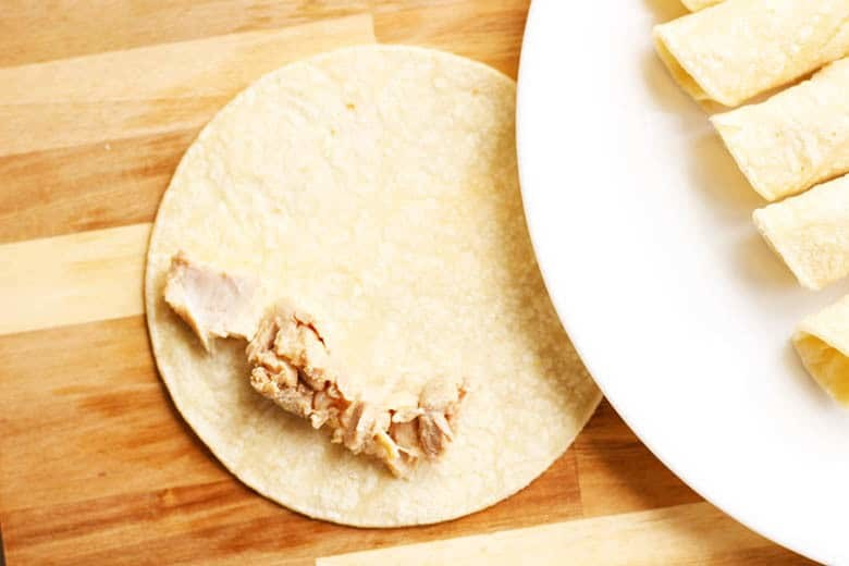 Easy Traditional Chicken Flautas Recipe. Just make your simple chicken filling, scoop on a corn tortilla, roll and shallow fry until golden brown. Serve with your favorite Latin American garnishes like salsa, guac, sour cream, cilantro & cheese.