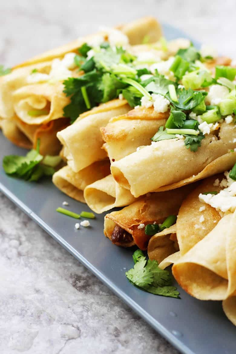 A plate of Chicken Mexican Flautas garnished with cilantro and cheese.