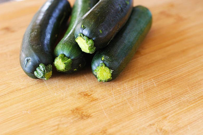 Four zucchini on a cutting board.