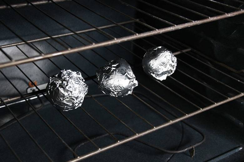 Three potatoes wrapped in foil in oven.