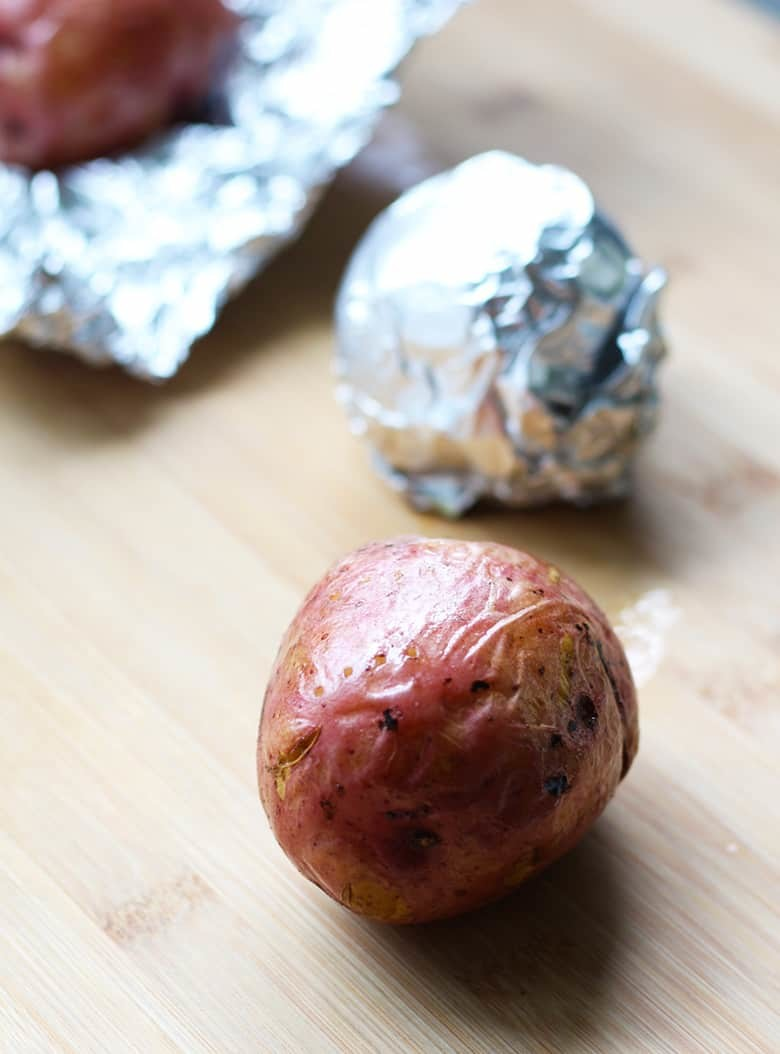 Baked potatoes on a cutting board.