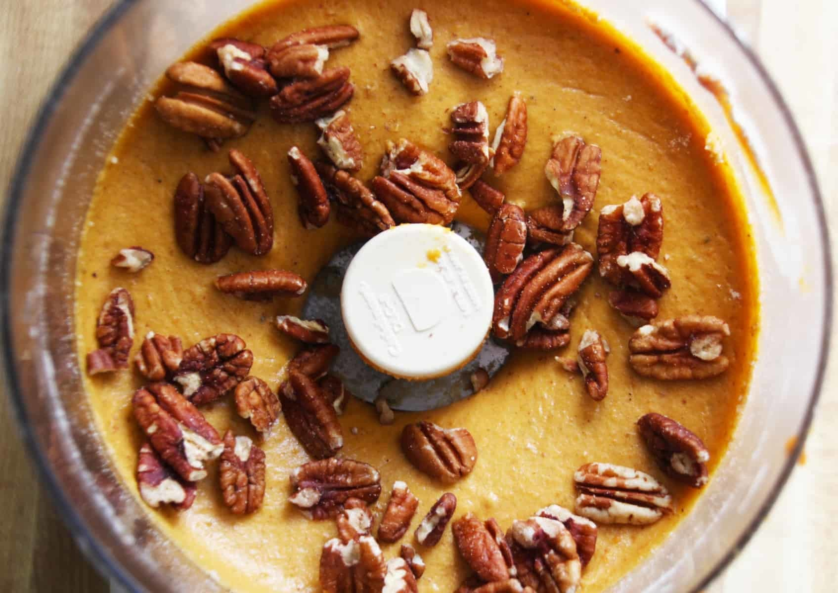 Food processor with batter and pecans.