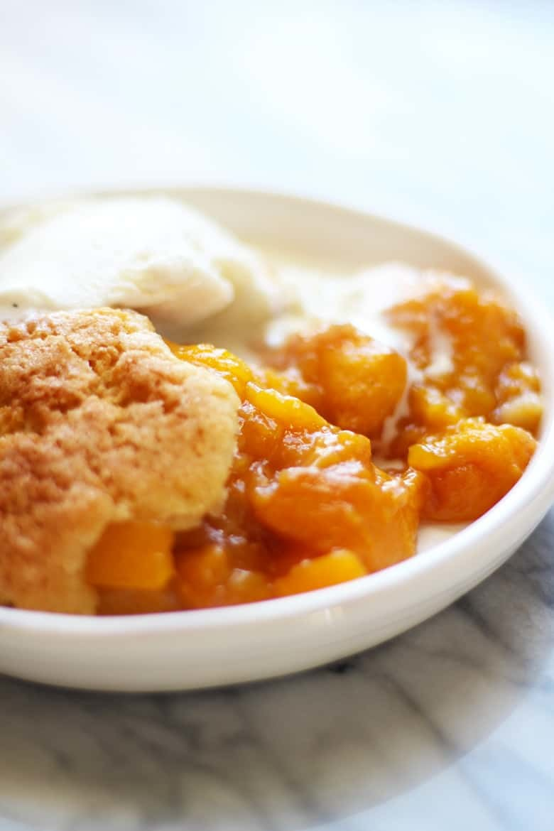 A bowl of French Peach Cobbler and ice cream.